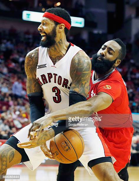 James Harden of the Houston Rockets reaches for the basketball behind James Johnson of the Toronto Raptors during their game at the Toyota Center on...