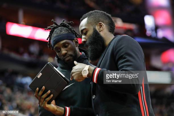 James Harden of the Houston Rockets reviews a play on a tablet with Briante Weber in the second half after the game at Toyota Center on January 4...
