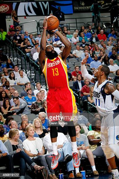 James Harden of the Houston Rockets shoots a jumper against Monta Ellis of the Dallas Mavericks on October 7 2014 at the American Airlines Center in...