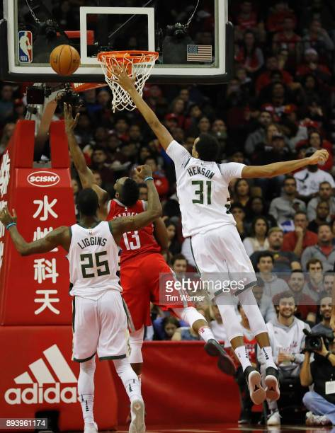 James Harden of the Houston Rockets shoots a lay up defended by John Henson of the Milwaukee Bucks and DeAndre Liggins in the second half at Toyota...