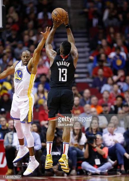 James Harden of the Houston Rockets shoots over Andre Iguodala of the Golden State Warriors at Toyota Center on March 13 2019 in Houston Texas NOTE...