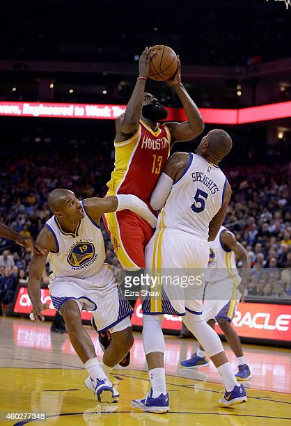 James Harden of the Houston Rockets shoots over Leandro Barbosa and Marreese Speights of the Golden State Warriors at ORACLE Arena on December 10...