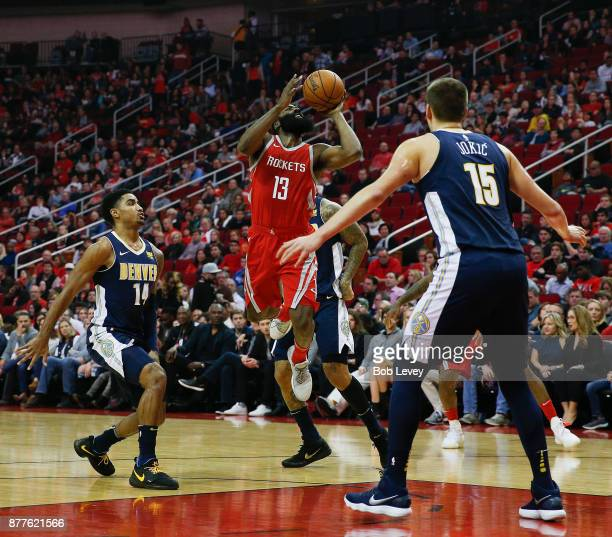James Harden of the Houston Rockets shoots over Nikola Jokic of the Denver Nuggets and Gary Harris at Toyota Center on November 22 2017 in Houston...
