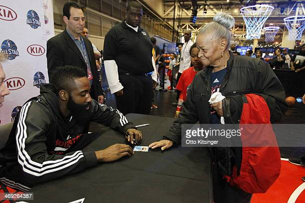 James Harden of the Houston Rockets signs an autograph for a fan at the Kia MVP Court during the 2014 NBA AllStar Jam Session at the Ernest N Morial...