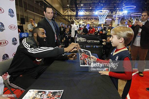 James Harden of the Houston Rockets signs an autograph for a young fan at the Kia MVP Court during the 2014 NBA AllStar Jam Session at the Ernest N...