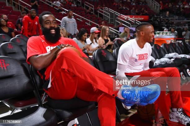 James Harden of the Houston Rockets smiles with Russell Westbrook of the Houston Rockets prior to a preseason game against the San Antonio Spurs on...