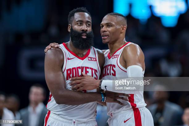 James Harden of the Houston Rockets speaks with Russell Westbrook during a break in the action against the Washington Wizards in the second half at...