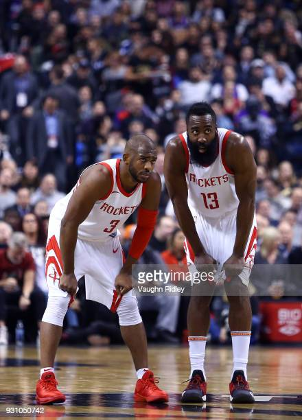 James Harden of the Houston Rockets speaks with teammate Chris Paul during the first half of an NBA game against the Tronto Raptors at Air Canada...