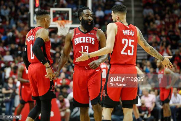 James Harden of the Houston Rockets talks with Austin Rivers in the second half against the Minnesota Timberwolves at Toyota Center on March 10, 2020...