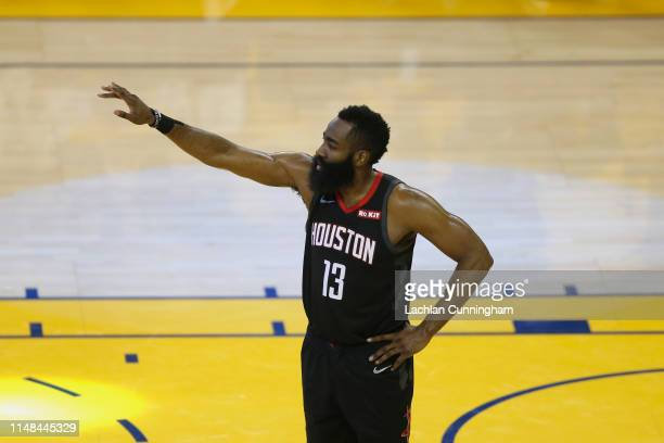 James Harden of the Houston Rockets talks with teammates during Game Five of the Western Conference Semifinals of the 2019 NBA Playoffs against the...