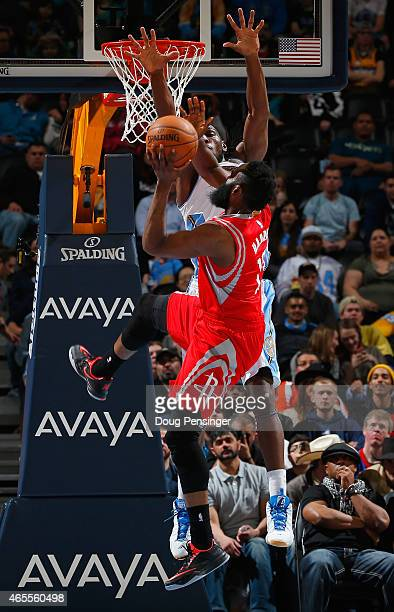 James Harden of the Houston Rockets tries to get off a shot against the defense of Kenneth Faried of the Denver Nuggets at Pepsi Center on March 7...