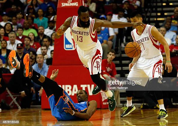 James Harden of the Houston Rockets trips over Kevin Durant of the Oklahoma City Thunder in the second period during a game at the Toyota Center on...
