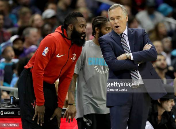 James Harden talks to his head coach Mike D'Antoni of the Houston Rockets during their game against the Charlotte Hornets at Spectrum Center on...