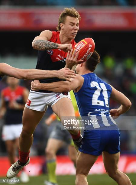 James Harmes of the Demons handballs whilst being tackled by Jy Simpkin of the Kangaroos during the round 19 AFL match between the North Melbourne...