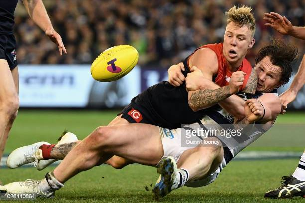 James Harmes of the Demons handballs whilst being tackled by Patrick Dangerfield of the Cats during the AFL First Elimination Final match between the...