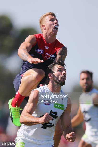 James Harmes of the Demons leaps on Simon White of the Blues for a high mark attempt during the JLT Community Series AFL match between the Melbourne...
