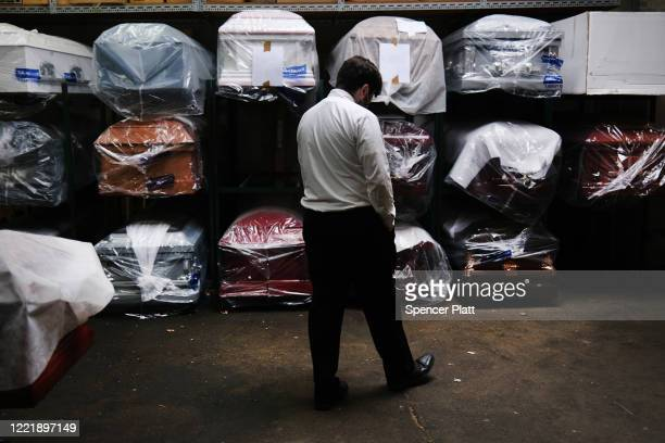 James Harvey tends tends to the inventory of pre-sold caskets at a funeral home on April 29, 2020 in New York City. The funeral home, which serves a...