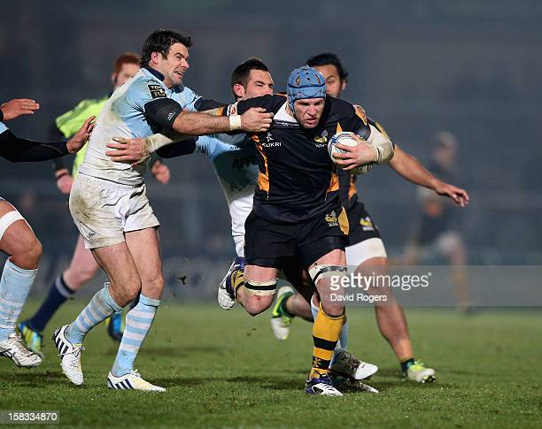 James Haskell of Wasps is tackled by Mike Phillips and Thibault Lacroix during the Amlin Challenge Cup match between London Wasps and Bayonne at...
