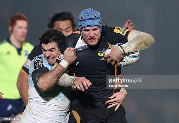 James Haskell of Wasps is tackled by Mike Phillips during the Amlin Challenge Cup match between London Wasps and Bayonne at Adams Park on December 13...