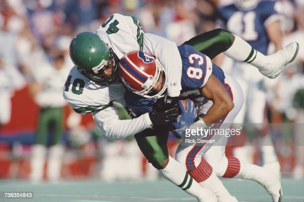 James Hasty defensive back for the New York Jets tackles wide receiver Andre Reed of the Buffalo Bills during their American Football Conference game...