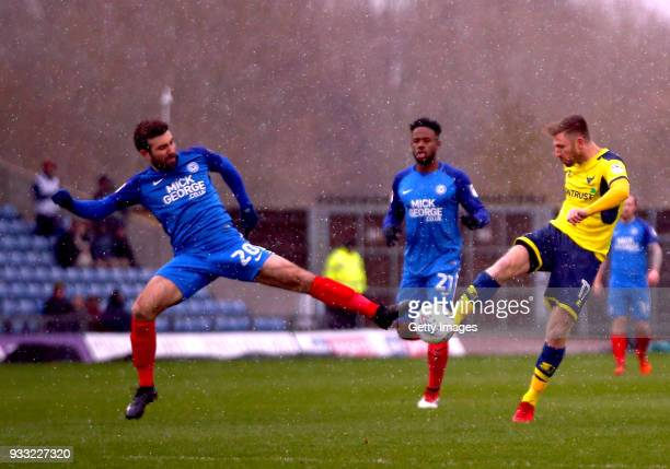 James Henry of Oxford United fires in a shot on goal under pressure from Michael Doughty of Peterborough United during the Sky Bet League One match...