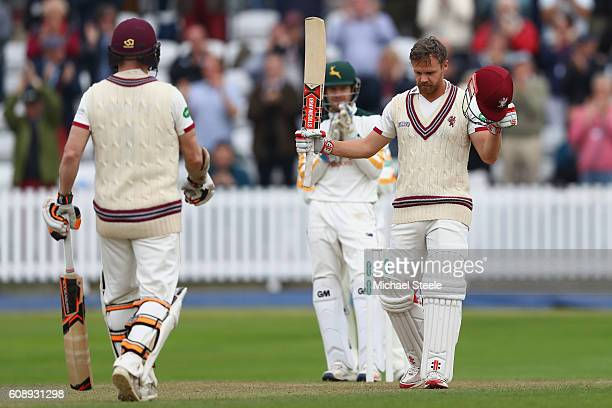 James Hildreth of Somerset raises his bat as he celebrates reaching his century with Chris Rogers during day one of the Specsavers County...