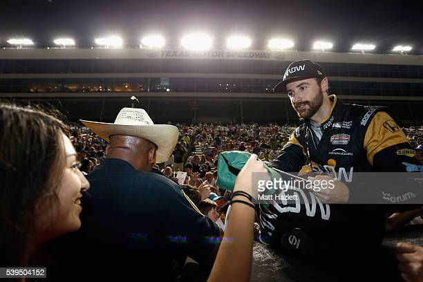James Hinchcliffe of Canada driver of the ARROW Schmidt Peterson Motorsports Chevrolet signs autographs for fans during a rain delay prior to the...