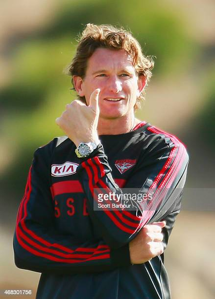 James Hird coach of the Bombers gives a thumbs up gesture to supporters in the crowd as they applaud as the Bombers come out to begin training during...