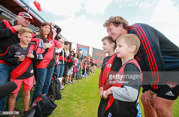 James Hird coach of the Bombers poses for photographs with supporters in the crowd who turned up to watch training after an Essendon Bombers AFL...