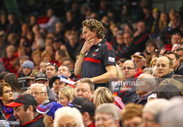 James Hird coach of the Essendon Bombers walks through Bombers supporters in the crowd as heads to speak to his players at three quarter time during...