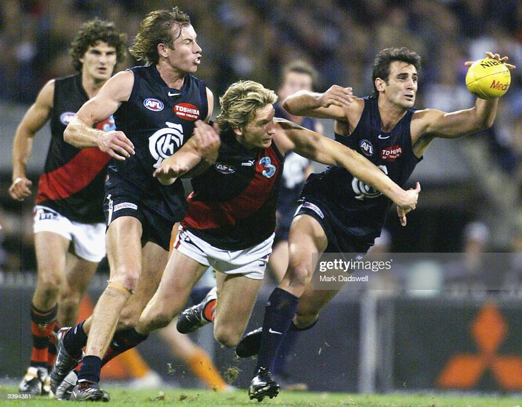 James Hird #5 for the Bombers contests with Scott Camporeale #16 for the Blues during the round four AFL match between the Carlton Blues and the Essendon Bombers at the Melbourne Cricket Ground April 16 2004 in Melbourne, Australia.