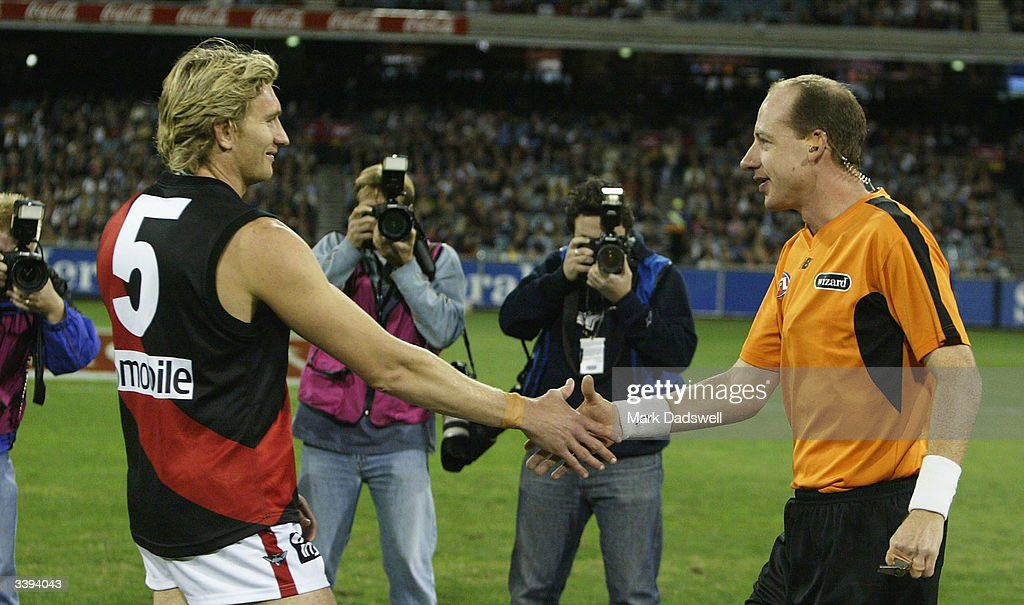 James Hird #5 for the Bombers shakes hands with umpire Scott McLaren during the round four AFL match between the Carlton Blues and the Essendon Bombers at the Melbourne Cricket Ground April 16, 2004 in Melbourne, Australia.