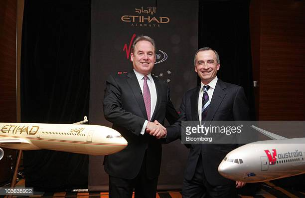 James Hogan chief executive officer of Etihad Airways PJSC left shakes hands with John Borghetti chief executive officer of Virgin Blue Holdings Ltd...
