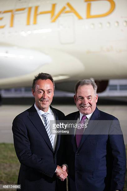 James Hogan chief executive officer of Etihad Airways PJSC right and Fabrice Bregier chief executive officer of Airbus shake hands while posing for...