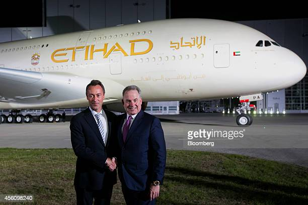 James Hogan chief executive officer of Etihad Airways PJSC right shakes hands with Fabrice Bregier chief executive officer of Airbus Group NV while...