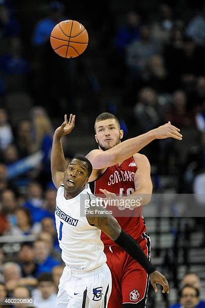 James Hunter of the South Dakota Coyotes slaps the ball away from Austin Chatman of the Creighton Bluejays during their game at CenturyLink Center...