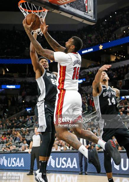 James Johnson of the Miami Heat drives for two in front of Rudy Gay of the San Antonio Spurs at ATT Center on December 06 2017 in San Antonio Texas...