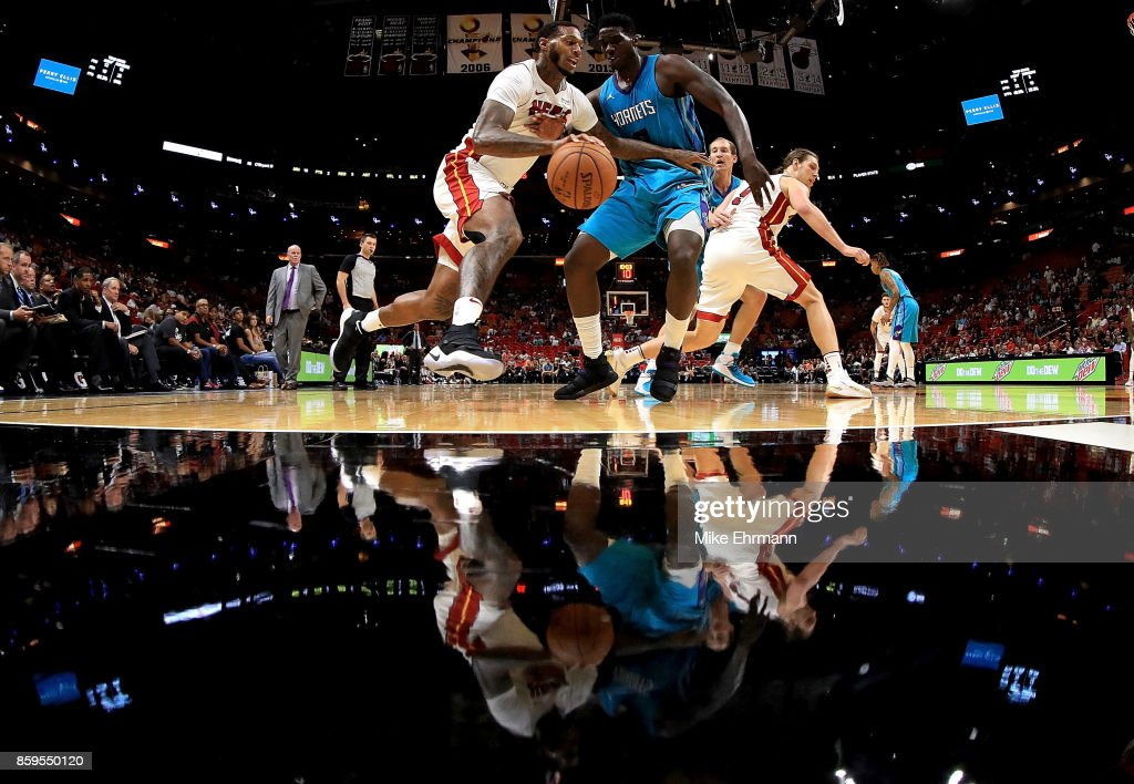 James Johnson #16 of the Miami Heat drives on Johnny O'Bryant III #8 of the Charlotte Hornets during a preseason game at American Airlines Arena on October 9, 2017 in Miami, Florida.