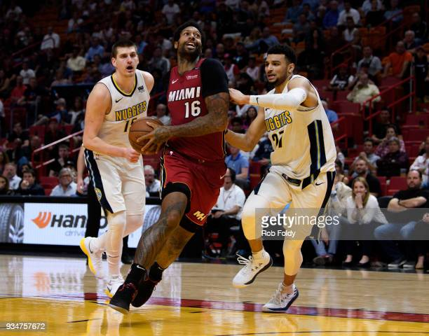 James Johnson of the Miami Heat drives past Nikola Jokic and Jamal Murray of the Denver Nuggets during the second half of the game at American...