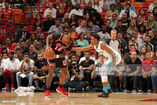 James Johnson of the Miami Heat handles the ball against Malik Monk of the Charlotte Hornets on December 1 2017 at American Airlines Arena in Miami...