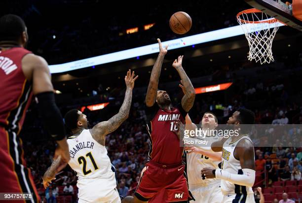 James Johnson of the Miami Heat is defined while shooting during the second half of the game against the Denver Nuggets at American Airlines Arena on...