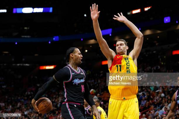 James Johnson of the Miami Heat throws a pass around Brook Lopez of the Milwaukee Bucks at American Airlines Arena on December 22 2018 in Miami...