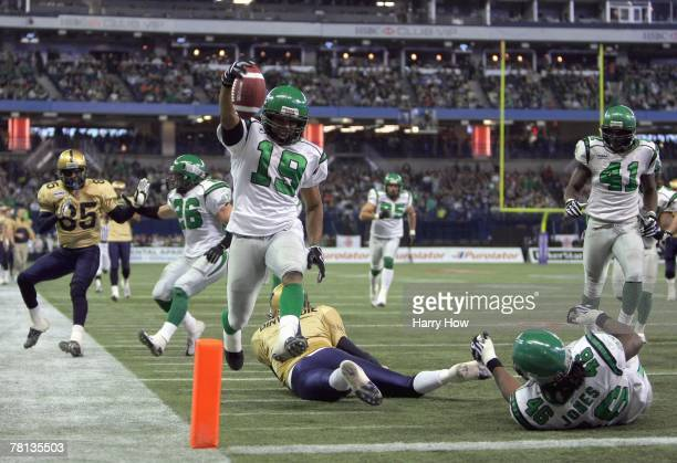 James Johnson of the Saskatchewan Rough Riders jumps over a fallen Ryan Dinwiddie after his interception to score a touchdown to tie the game 7-7...