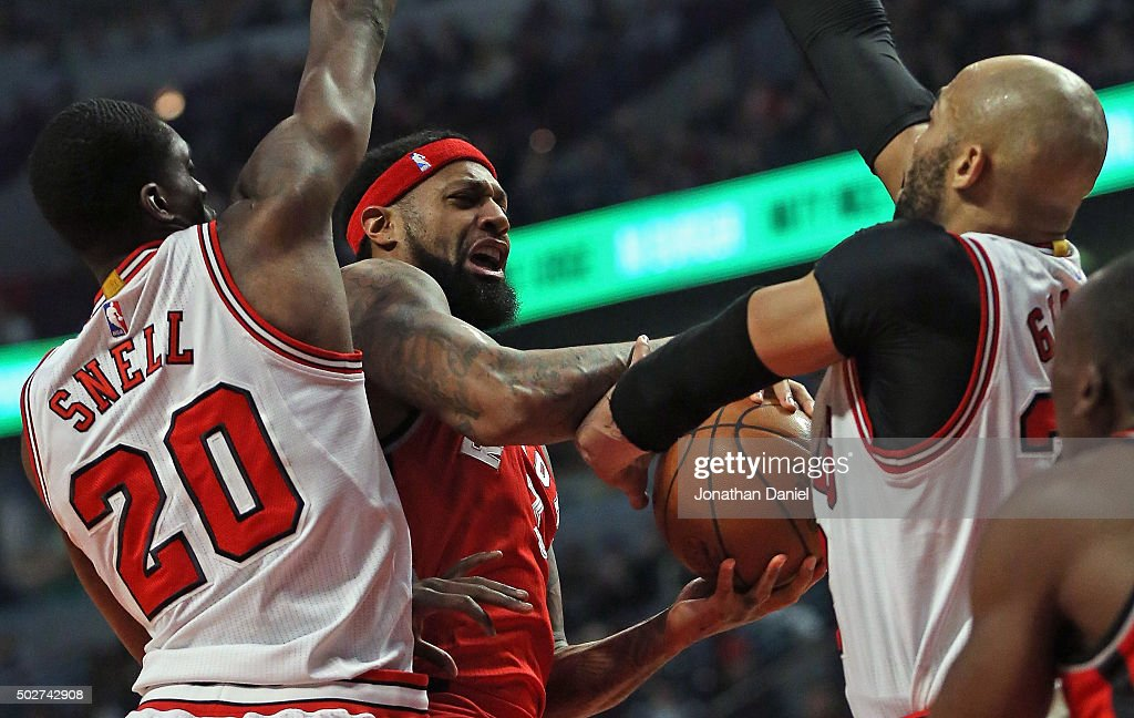 James Johnson #3 of the Toronto Raptors tries to get off a shot between Tony Snell #20 and Taj Gibson #22 of the Chicago Bulls at the United Center on December 28, 2015 in Chicago, Illinois.
