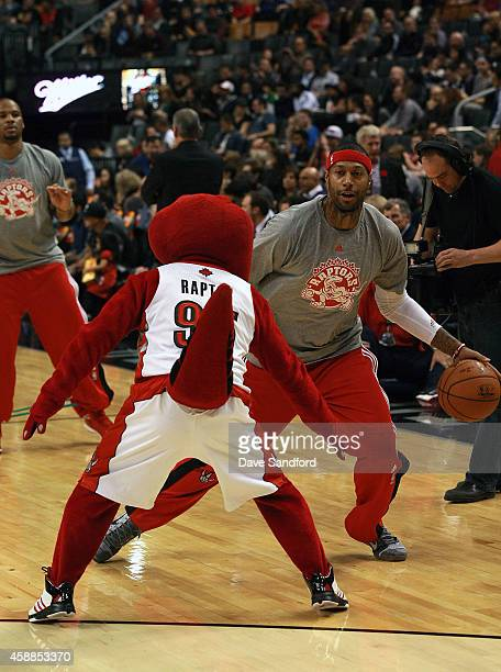 James Johnson of the Toronto Raptors warms up to face the Oklahoma City Thunder as the Toronto Raptors mascot defends during their game at Air Canada...