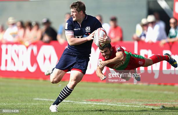 James Johnstone of Scotland is tackled by Joao Belo of Portugal in the Bowl quarter final match during the Emirates Dubai Rugby Sevens HSBC World...