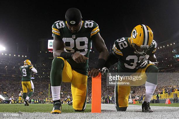 James Jones of the Green Bay Packers and Chris Banjo kneel in the end zone before the start of the game against the Chicago Bears at Lambeau Field on...