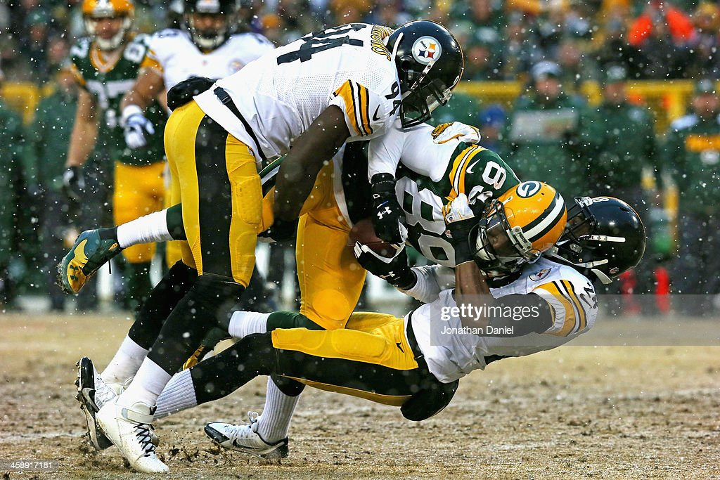 James Jones #89 of the Green Bay Packers is dropped by Lawrence Timmons #94 and Ike Taylor #24 of the Pittsburgh Steelers at Lambeau Field on December 22, 2013 in Green Bay, Wisconsin.