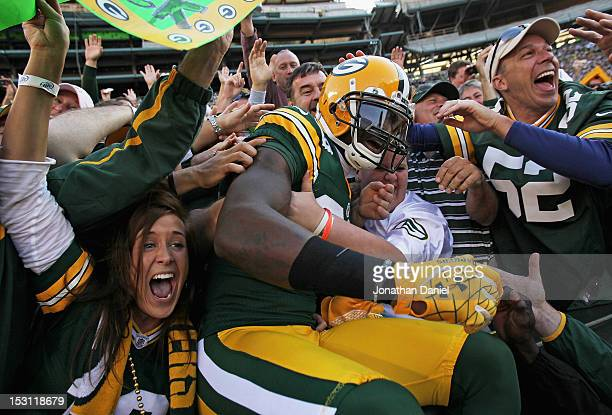 James Jones of the Green Bay Packers leaps into the stands after catching a touchdown pass against the New Orleans Saints at Lambeau Field on...