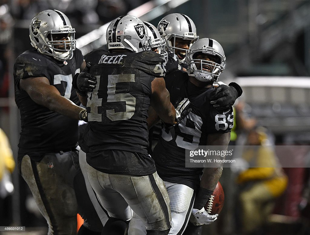 James Jones #89 of the Oakland Raiders celebrates with teammates Marcel Reece #45 and Menelik Watson #71 after scoring a touchdown in the fourth quarter of the game against the Kansas City Chiefs at O.co Coliseum on November 20, 2014 in Oakland, California.